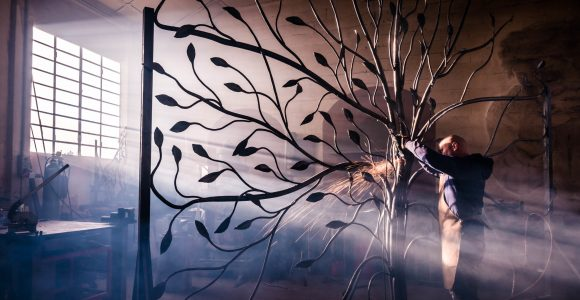 Blacksmith artist working in his smithy studio creating a gate-tree
